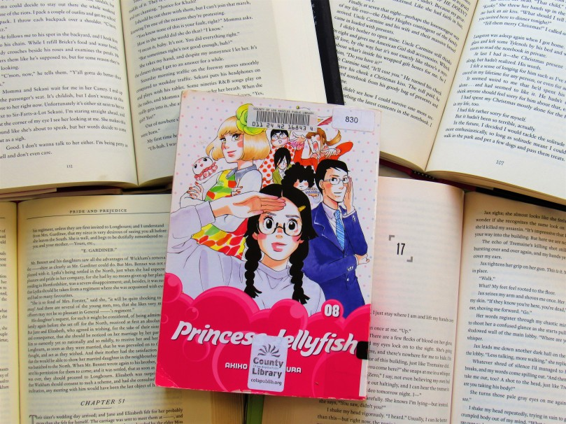 Picture of princess jellyfish volume 8 against open book pages.