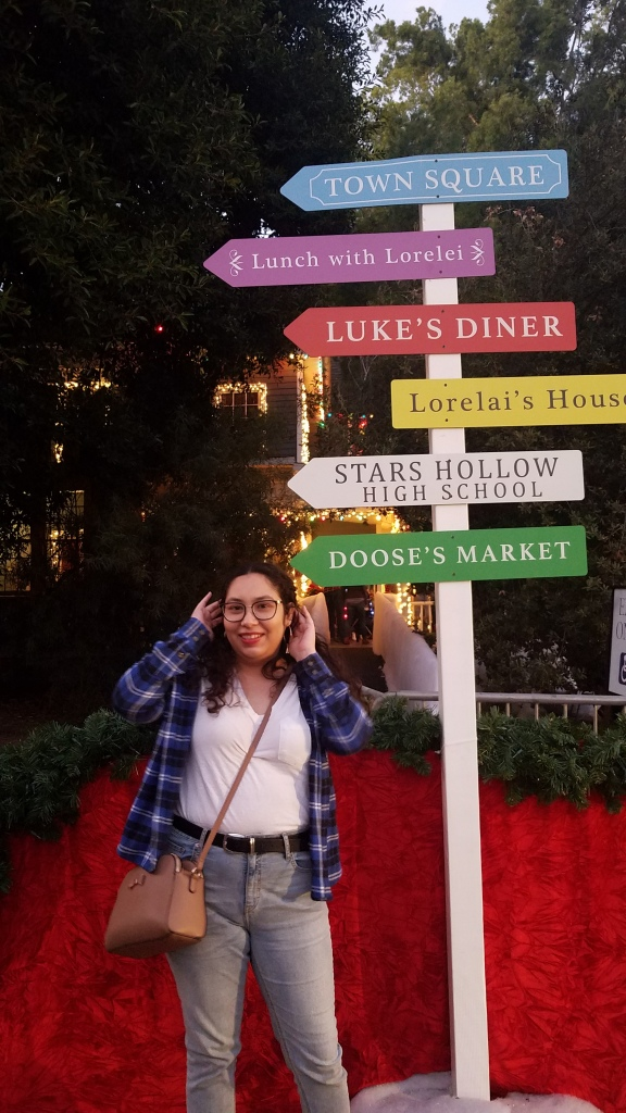 An excited young woman in gold hoops stands in front of a sign with arrows pointing towards Town square, Lunch with Lorelei, Luke's diner, Lorelai's house, Star's Hollow High school, and Doose's Market.