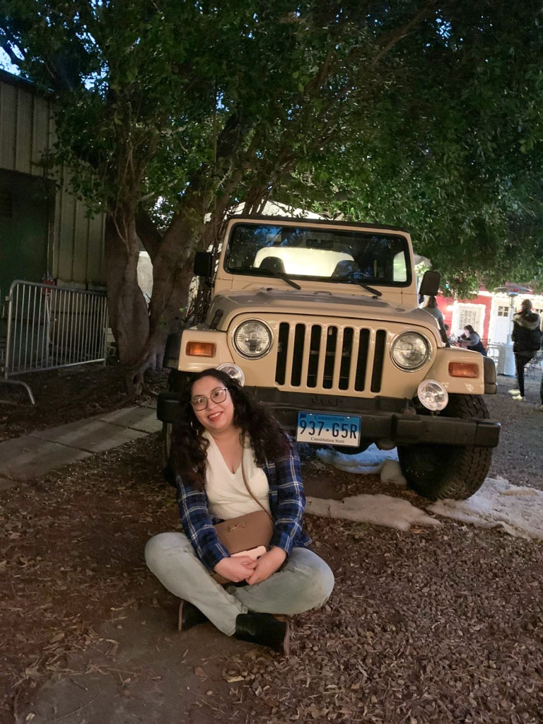A very excieted young woman sits cross legged in front of Lorelei's beige jeep.